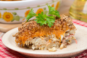 Gratin with fish and pumpkin on a plate, close-up