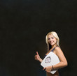Beautiful young woman with weight scale on blackboard background