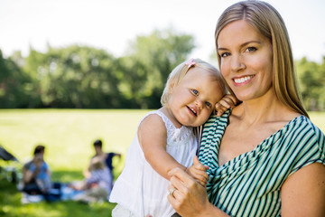 Happy Mother Carrying Cute Daughter In Park