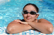Woman relaxing at the side of a swimming pool