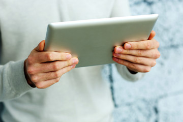Closeup image of male hands holding tablet computer