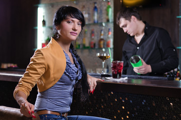 Independent young woman relaxing alone at the bar