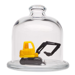 Toy yellow excavator in a glass dome
