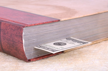 closed brown book with a bookmark 100 USD