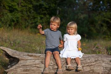 Boy and girl sitting on log