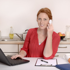 Hübsche rothaarige Frau telefoniert im Homeoffice