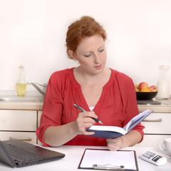 Hübsche rothaarige Frau arbeitet im Homeoffice