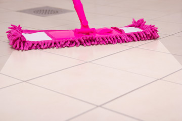 cleaning the floor with pink mop