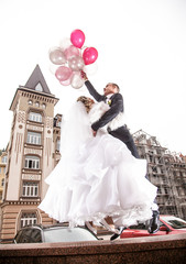 Young bride and groom flying on helium balloons in the city
