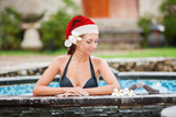 Beautiful woman with santa hat relaxing in jacuzzi at spa center
