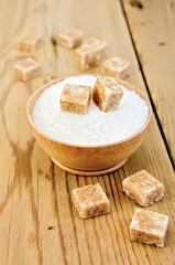 Sugar brown and white in a wooden bowl on a board