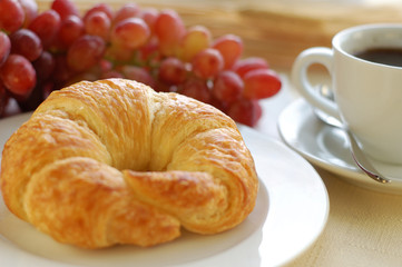 Breakfast with croissant, coffee and fruit.
