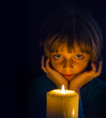 sad little girl with a candle