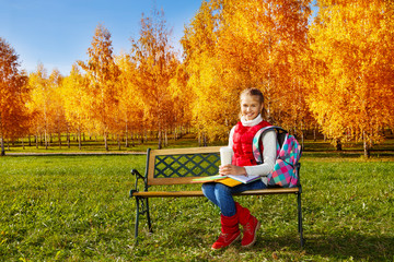 Girl with textbooks and coffee mug in park