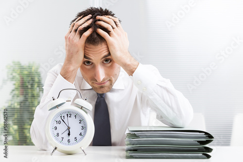 Stressed business man under time pressure cries in office