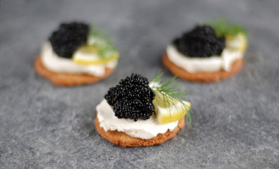 Three black caviar appetizers