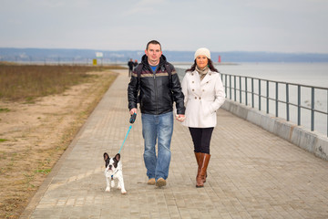 Couple on the walk with dog at the sea