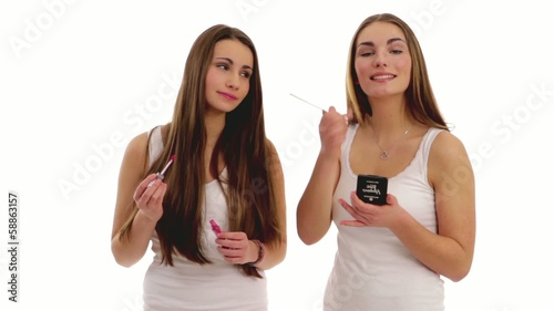 two beautiful brunette girls putting on make up