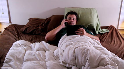 Man in bed on phone and on tablet, multitasking