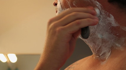 Man Shaving Face in bathroom