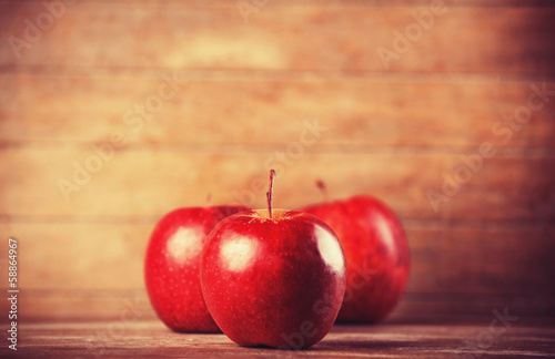 Three red apples on wooden table