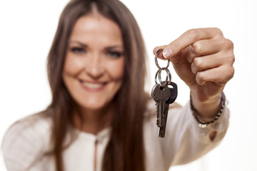 smiling young woman holding in her hand a bunch of keys