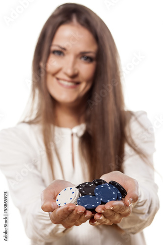 smiling young woman holding a pile of chips in her hands