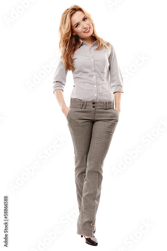 Cheerful businesswoman with hands in pockets