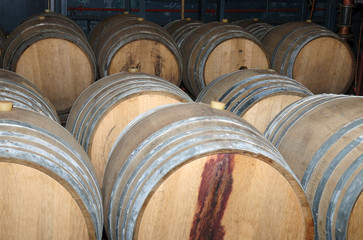 Wine barrels in arrangement waiting in a cellar