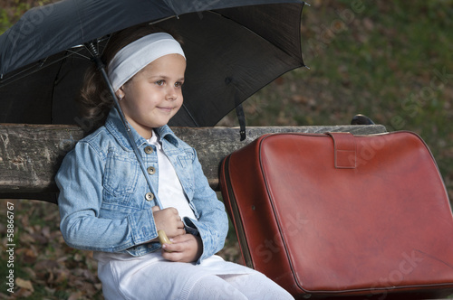 Portrait of cute little girl sitting on bench in park