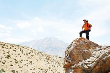 Tourist hiker hands up on mountain top
