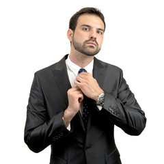 Businessman putting on a necktie over white background