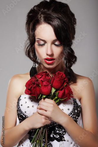 Young Beauty Smelling Bouquet of Red Roses. Pleasure & Harmony