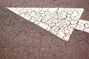 Abstract Close Up Of Arrow On Road Surface
