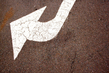 Angled White Painted Arrow On Road Surface