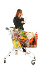 Woman with full shopping cart reading receipt