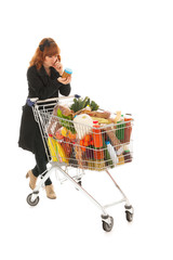 Woman with full shopping cart reading label