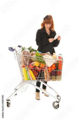 Woman with full shopping cart reading shopping list
