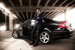 man in suit leaning against black expensive car under bridge