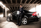 man in suit leaning against black expensive car under bridge