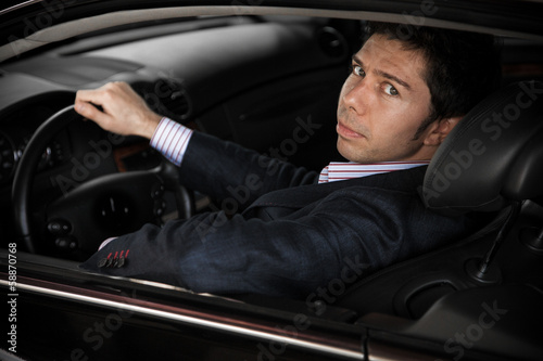 portrait of elegant driver looking though open window of car