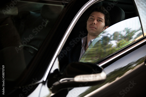 Handsome driver driving luxurious black car with opened window