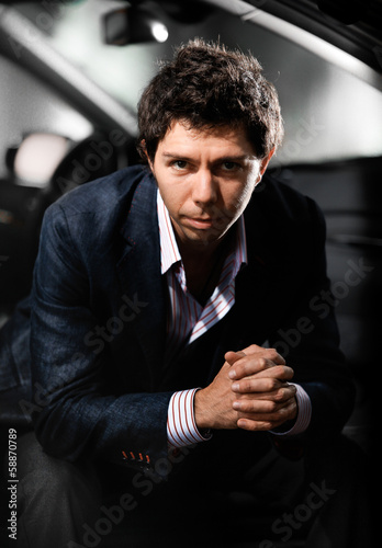 man in suit sitting on passenger seat and looking at camera