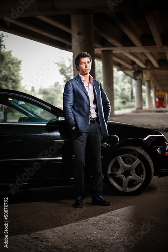 Handsome elegant man in suit posing against black luxury car