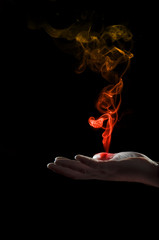 Hand holding a smoke shape colored on red an yellow