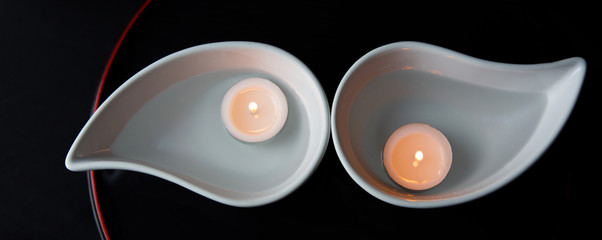 Candle in ceramic container over black background