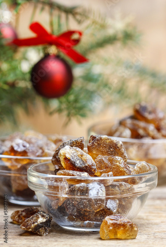 Granulated brown sugar in transparent glass bowl on wooden table