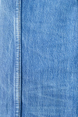 Seam on blue jeans background.