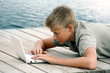 Boy writing with computer at the sea