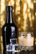 Baileys liqueur in bottle and glass on golden background